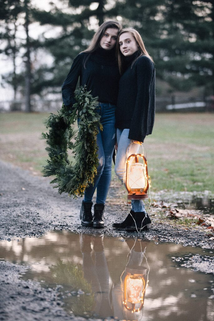 sister at dusk with lantern and christmas wreath Loudoun County mini sessions