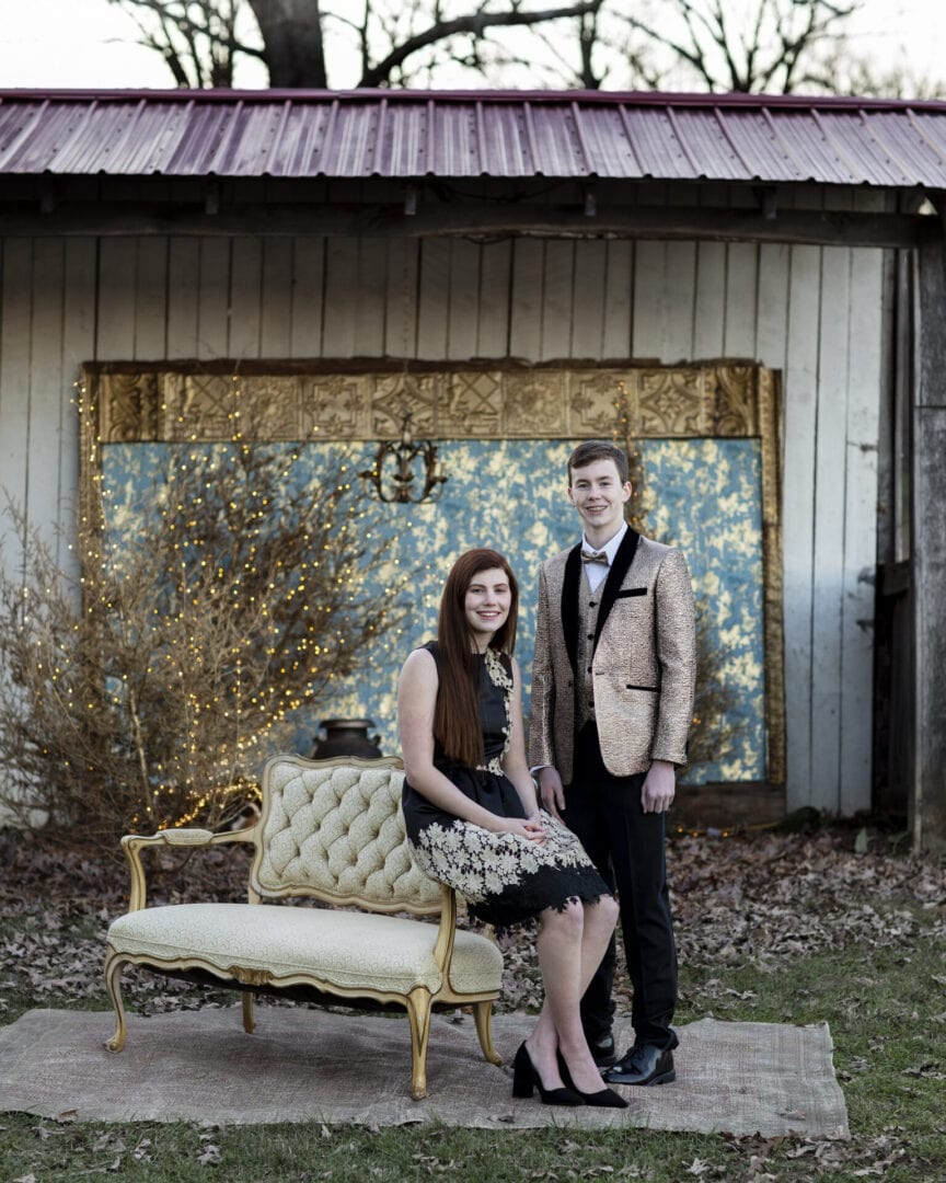 Formal brother and sister at Christmas time in a rustic and elegant country setting
