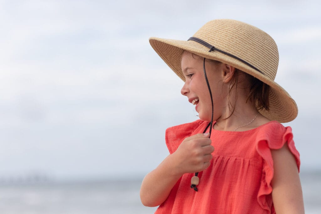 Girl laughing with hat on beach