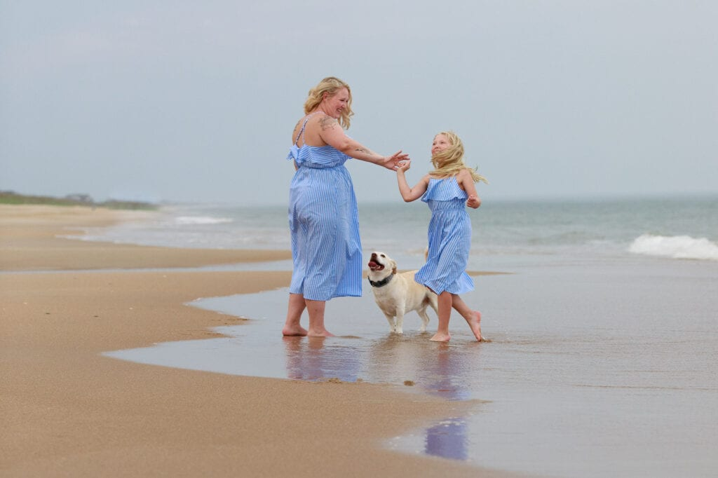 mother and daughter with dog enjoy the evening on the beach sanderling nc