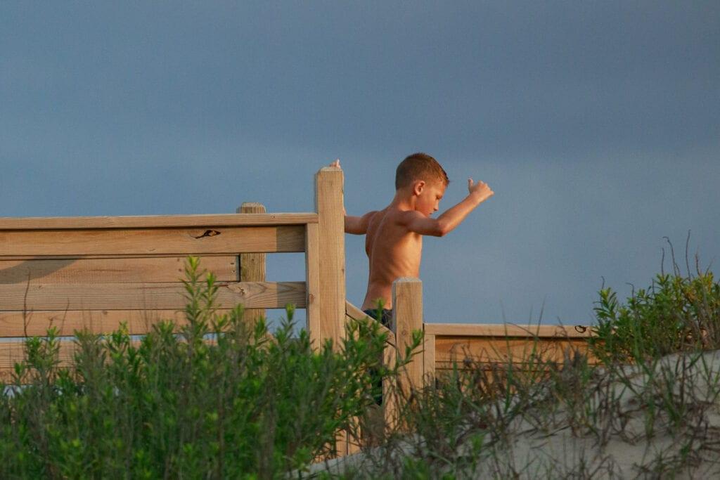 Boy running off the beach on walkway, Corolla NC