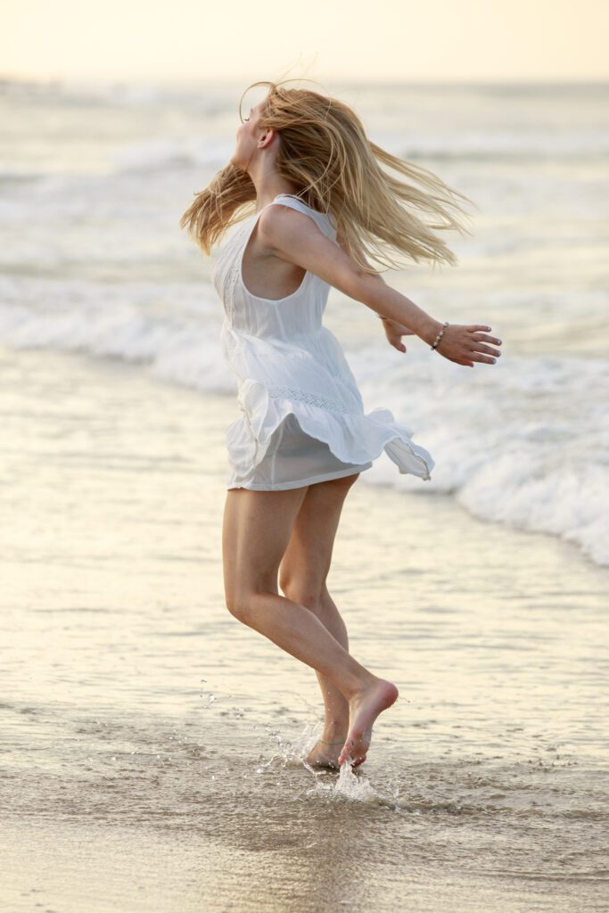 girl twirling on the ocean shore line Nags head nc