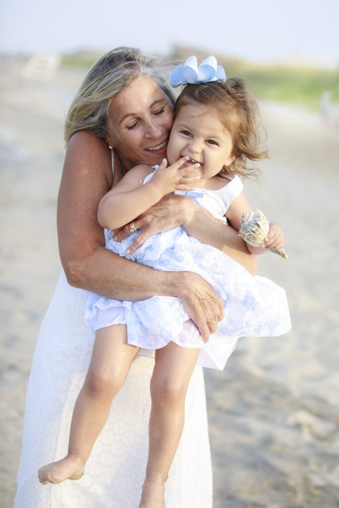 grandmother and granddaughter sharing love on the beach in Duck nc