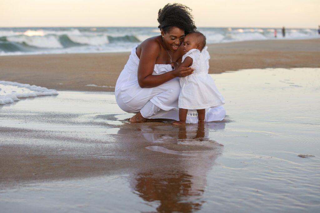 Beautiful mom with baby  girl on the beach