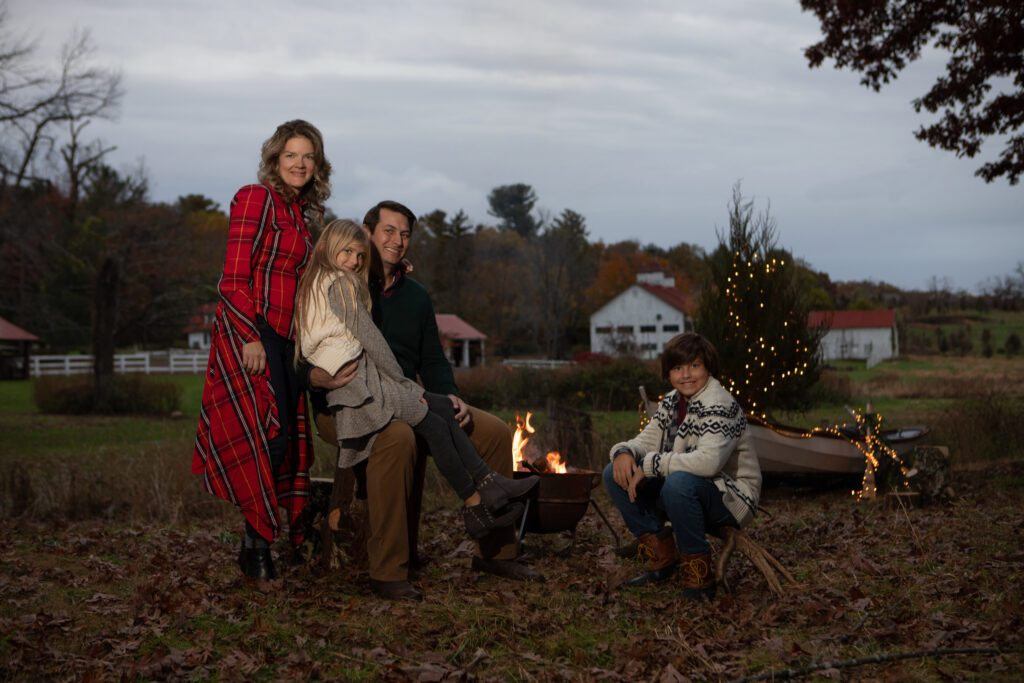Family at dusk in rustic setting with camp fire